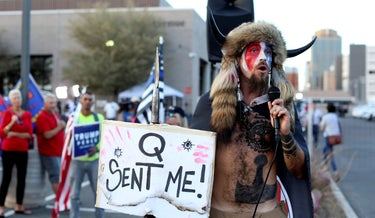 QAnon believer Jake Angeli speaks to a crowd of President Donald Trump supporters in Phoenix, AZ, the day after the U.S. election last year.