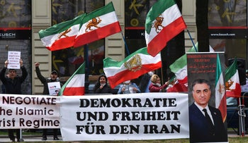 A sign reads 'Democracy and Freedom for Iran' at a protest outside the Viennese hotel where closed-door nuclear talks with Iran are taking place, yesterday.