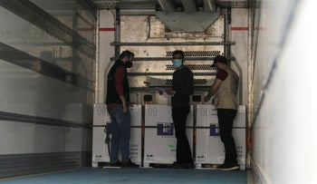 Healthcare workers stand next to boxes containing coronavirus vaccines at Bab al-Hawa crossing at the Syrian-Turkish border, on Wednesday.