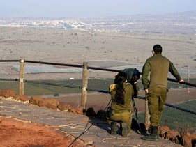 Israeli soldiers look towards Syria across the border from Mount Bental, November 2020.