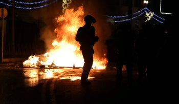 Israeli police officers stand next to a burning barricade during clashes in Jerusalem yesterday.