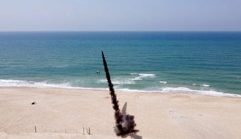 A rocket is launched into the Mediterranean Sea off the Gaza Strip during an anti-Israel military drill by the Palestinian Mujahideen Brigades, in the Gaza Strip, today.