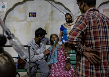 A woman with difficulties breathing brought on by COVID-19 receives free oxygen at a gurdwara (Sikh temple) in Ghaziabad, India this month