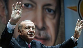 Turkish President Recep Tayyip Erdogan holds up his hand in the Rabia or Rabaa four finger sign as he greets the crowd during AK Party's extended meeting in Ankara, last year