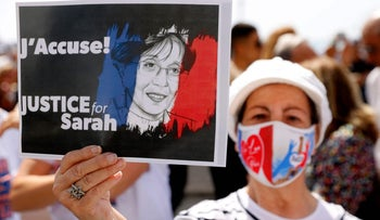 """A Franco-Israeli woman raising a placard during a rally in front of the French Embassy in Tel Aviv earlier this week. The message says """"J'accuse"""" and """"Justice for Sarah."""""""