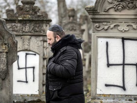 A member of the Jewish community walks among defaced gravestones at the Jewish cemetery of Herrlisheim, near Strasbourg, eastern France