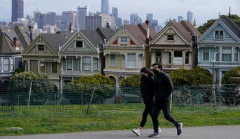 People wearing masks walk along a row of historical Victorian homes in San Francisco.