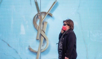 A women walks past an ad for the luxury fashion brand Yves Saint Laurent, Jerusalem, this month. The subject of the photo has no connection with the content of this article.