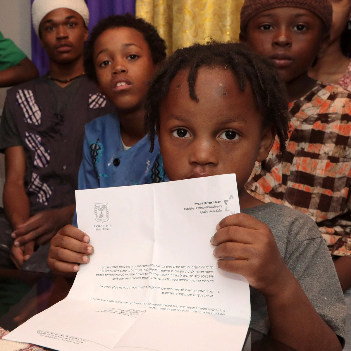 A young member of the Hebrew Israelite community in Dimona holding the deportation letter from the government.