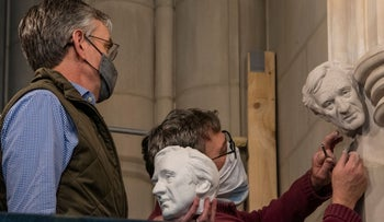 Sculptor Chas Fagan holds a clay model of a bust of Elie Wiesel and watches as stonemason Sean Callahan carves it into the walls of the National Cathedral in Washington.
