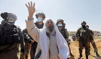 A Palestinian demonstrator in front of Israeli troops during a March protest against Israeli settlements, in Yatta.