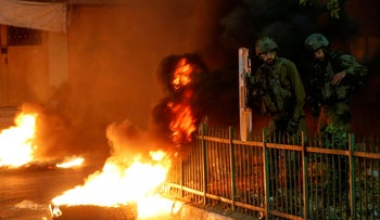 Israeli soldiers stand next to burning tires as Palestinians take part in an anti-Israel protest over tension in Jerusalem, in Hebron, this week.