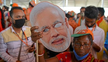 A Bharatiya Janata Party (BJP) supporter holds a mask showing Indian Prime Minister Narendra Modi as he addresses a campaign rally in West Bengal this month