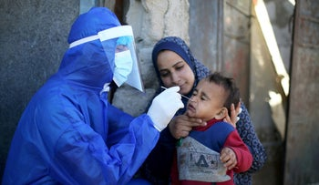 A Palestinian medical worker collecting a swab sample from a boy to be tested for COVID in the southern Gaza Strip in January.
