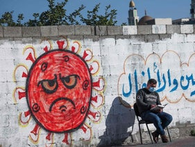 A Palestinian reading the Koran in front of a coronavirus-inspired mural during Ramadan in Gaza City earlier this month.