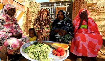 Women sit together as they prepare food for their families in Khartoum, Sudan in March.