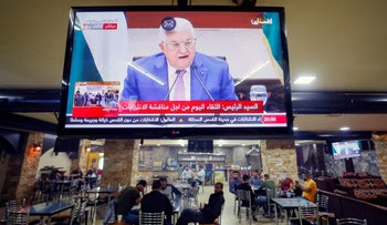 A screen displaying a live broadcast of Palestinian President Mahmoud Abbas's speech, in a coffee shop in Ramallah, today.