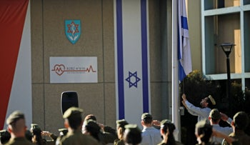 Israeli soldiers stand in formation as the national flag is lowered to half-mast at the Tzrifin military base, today.