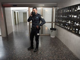 A police officer stands in the lobby of the apartment building where Svetlana Belkin was found dead in her home, Saturday night