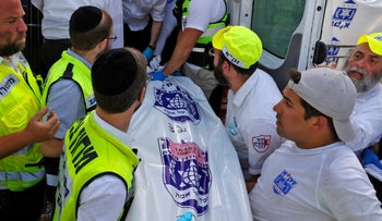 Israeli rescue teams carry a body bag into an ambulance at the scene of a stampede.
