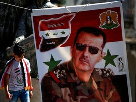 A youth walks past a banner depicting Syrian President Bashar Assad, last month.