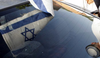 Israel's flag reflects back from a car's windshield, in 2005.