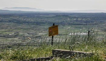 A sign warning against landmines in the Golan Heights along the border fence with Quneitra, April 2021.
