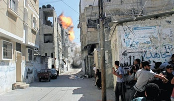Palestinians take cover during an Israeli strike on a building in the Rafah refugee camp, southern Gaza Strip during the summer 2014 war in the enclave.