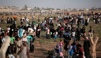 Thousands of Syrian refugees walk in order to cross into Turkey, as seen from the Turkish side of the border, in 2015.
