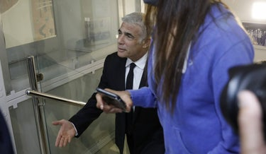 Yesh Atid leader Yair Lapid prepares to deliver remarks, today.