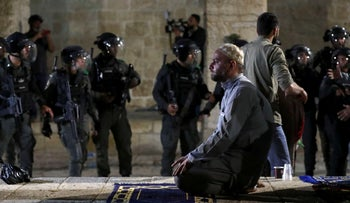 A Palestinian man prays as Israeli police gather during clashes at the Al-Aqsa Mosque, amid tension in the Sheikh Jarrah neighbourhood, in Jerusalem's Old City, yesterday.