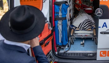An ultra-Orthodox man looks into an ambulance at the funeral of Avraham Daniel Ambon, 21, from Argentina, who died in the Mount Meron disaster, on Monday.