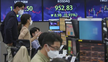 Currency traders watch monitors at the foreign exchange dealing room in Seoul, South Korea, last week.