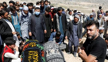 Relatives mourn next to coffins of two victims of yesterday's explosion during a mass funeral ceremony in Kabul, Afghanistan.