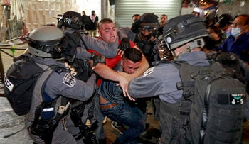 Israeli security forces clash with Palestinian protesters outside the Damascus Gate in Jerusalem's Old City, tonight.