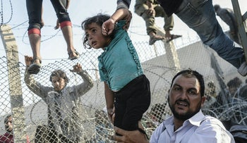 A Syrian child fleeing the war is lifted over border fences to enter Turkish territory illegally, near the Syrian border crossing at Akcakale in Sanliurfa province in 2015