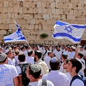 As Israel marks Jerusalem Day, Jewish men wave Israeli flags at the Western Wall, the holiest site where Jews are allowed to pray, in the old city of Jerusalem