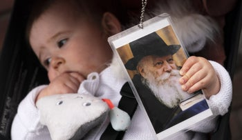 A baby girl clutching a photo of the late Rabbi Menachem Schneerson during a Lag Ba'omer celebration in front of the Chabad Lubavitch World Headquarters in New York last month.