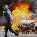 An Israeli firefighter walks next to cars hit by a rocket fired from Gaza Strip, in the southern Israeli town of Ashkelon, May 11, 2021.