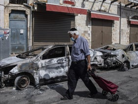 A Jewish man passing cars torched after a night of violence between Arab-Israeli protesters and Israeli police in Lod, yesterday.