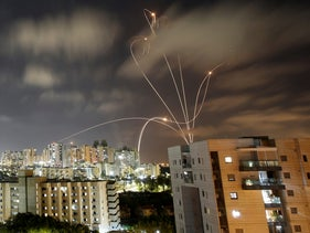 Streaks of light are seen as Israel's Iron Dome anti-missile system intercepts rockets launched from the Gaza Strip towards Israel, today.