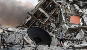 Rescuers and people gather in front of the debris of Al-Sharouk tower that collapsed after being hit by an Israeli air strike, in Gaza City, yesterday.