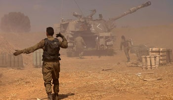 Israeli soldiers fire toward the Gaza Strip from their position near Sderot, today.