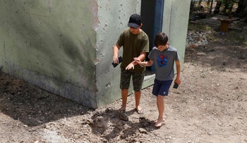 Youngsters at Kibbutz Nahal Oz examining the blast marks caused by a Gazan missile last month.