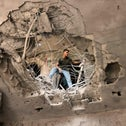 A Palestinian man checks the damage caused by an Israeli air strike at the Islamic National Bank of the Palestinian Hamas movement in Khan Yunis, today.
