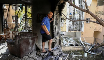 A member of Sror family inspect the damage of their apartment after being hit by a rocket fired from the Gaza Strip over night, in Petah Tikva.