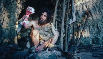 A primeval caveman holding a bone and hitting a rock with it.