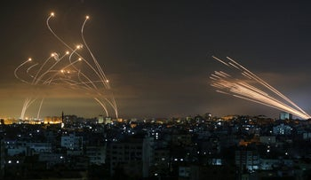 Gaza rockets (right) fired towards Israel from Beit Lahia met by Iron Dome missile defense