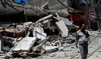 A man looks at the remains of destroyed building after being hit by Israeli airstrikes in Gaza City, yesterday.