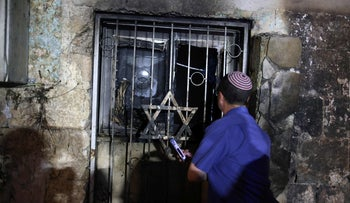 An Israeli man looks inside a synagogue after it was set on fire by Arabs in the mixed Jewish-Arab city of Lod, today.